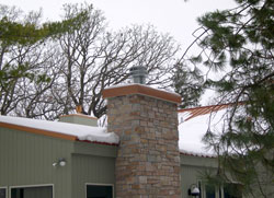 Before <br> on this beautiful wooded home the grey industrial chimney pipe sticks out like a sore thumb.